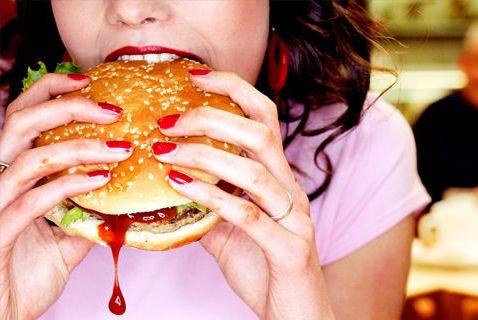 кушает гамбургер с кетчупом